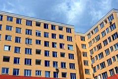 一个大房子的门面有棕色颜色公寓和窗口的反对灰色云彩背景的  免版税库存图片