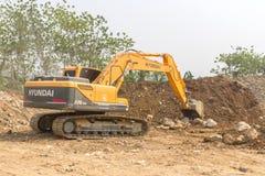一个大挖掘机掘土工在新建工程站点运作 库存图片