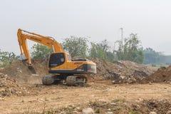 一个大挖掘机掘土工在新建工程站点运作 免版税库存图片