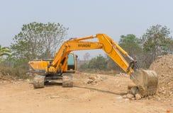 一个大挖掘机掘土工在新建工程站点运作 免版税库存照片