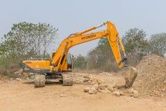 一个大挖掘机掘土工在新建工程站点运作 库存照片