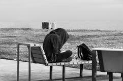 一个大敞篷的一个少年坐长凳由海并且读书 库存照片