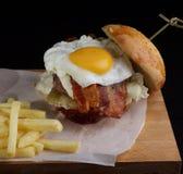 一个大汉堡用炒蛋、乳酪和一只鸡在旁边炸薯条 图库摄影
