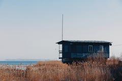 一个大湖的岸的温室 在草和水中的小船驻地 免版税库存照片