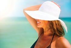 一个大白色帽子的妇女晒黑在海滩的 免版税库存照片