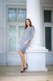一个大白色房子的背景的一名端庄的妇女 户外一双灰色礼服和黑鞋子的美丽的夫人 图库摄影