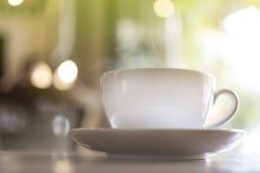 一个大白色杯子与蒸的热的饮料在与树bokeh的桌上在咖啡店 库存图片