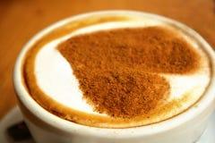 一个大白色杯子的特写镜头与艺术设计心脏的热的咖啡热奶咖啡对此站立在木背景的,爱概念 图库摄影