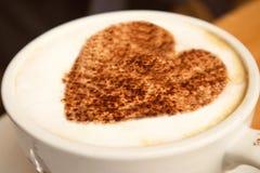 一个大白色杯子的特写镜头与艺术设计心脏的热的咖啡热奶咖啡对此站立在木背景的,爱概念 库存照片