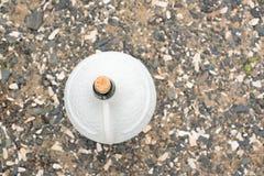 一个大白色水罐在海小卵石背景的酒  免版税库存照片
