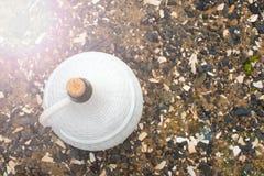 一个大白色水罐在海小卵石背景的酒  免版税库存图片