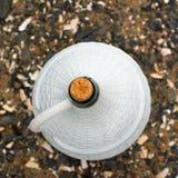 一个大白色水罐在海小卵石背景的酒  图库摄影