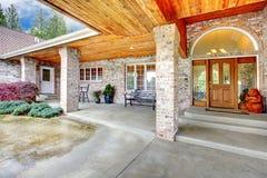 一个大砖房子的舒适入口门廊 与具体地板和砖专栏的露台地区 免版税图库摄影