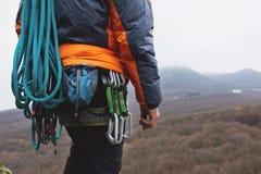 一个大腿登山人的特写镜头用在传送带的设备,在岩石的立场 图库摄影