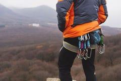 一个大腿登山人的特写镜头用在传送带的设备,在岩石的立场 库存图片