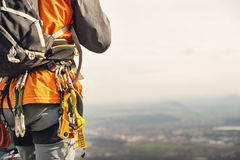 一个大腿登山人的特写镜头用在传送带的设备,在岩石的立场 免版税图库摄影