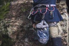 一个大腿登山人的特写镜头用在传送带的设备,在岩石的立场 免版税库存图片
