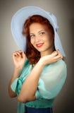 一个大蓝色帽子的女孩在工作室 免版税库存照片