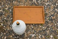 一个大酒水罐和一个木盘子在背景海小卵石 库存图片
