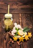 一个大金属螺盖玻璃瓶在木背景的柠檬茶 绿茶用香料 杯子热茶 复制空间 库存照片