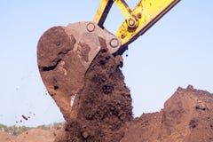 一个大铁挖掘机桶在道路设施建造场所收集并且倾吐沙子瓦砾和石头在猎物 库存照片