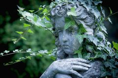 一个天使的古色古香的雕塑与常春藤的反对黑暗的背景 库存照片