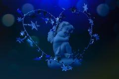 一个天使的小雕象在蓝色背景的 免版税库存照片