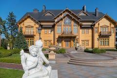一个天使的白色雕象在一个大阳台的在一个大木房子附近在有胡同的一个公园 免版税库存照片