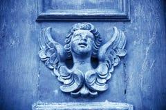一个天使的雕塑在一个木门的在意大利 免版税库存图片