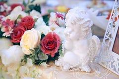 一个天使的雕象在内部的与装饰假日的花 图库摄影