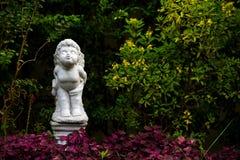 一个天使立场和亲吻的白色小雕象在的庭院家 库存照片