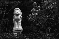 一个天使立场和亲吻的白色小雕象在的庭院家 免版税图库摄影