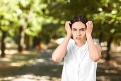 一个失望的女孩拿着她的在误解的头 一件女衬衫的一个少妇在绿色背景 企业夫人在公园 免版税库存照片
