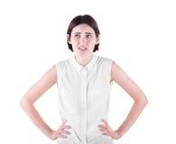 一个失望的女孩 一个迷茫的女孩用在臀部的手 在白色背景隔绝的一位恼怒的女性 通信问题 库存照片