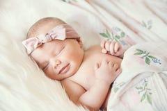 一个套的睡觉的微笑的新出生的婴孩在白色毯子 库存图片
