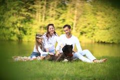 一个女儿和一个怀孕的妈妈的愉快的父亲野餐的 免版税库存图片