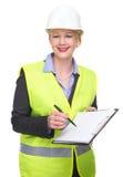 一个女商人的画象安全背心和安全帽文字的在空白的剪贴板 免版税库存图片