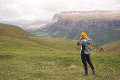 一个女孩为高原照相在一座高山顶部在一多云天 观点的后边女孩 库存照片