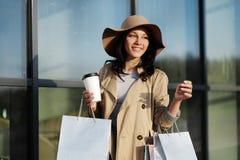 一个女孩从与包裹和咖啡杯的一个购物中心走 图库摄影