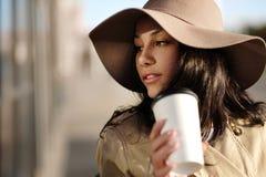 一个女孩从与包裹和咖啡杯的一个购物中心走 库存照片