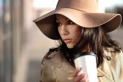 一个女孩从与包裹和咖啡杯的一个购物中心走 库存图片