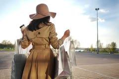 一个女孩从与包裹和咖啡杯的一个购物中心走 免版税库存图片