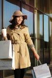 一个女孩从与包裹和咖啡杯的一个购物中心走 免版税库存照片