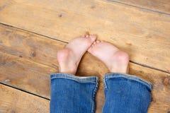一个女孩佩带的牛仔裤的赤脚 免版税库存图片