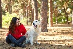 一个女孩使用与她的金毛猎犬 免版税库存照片