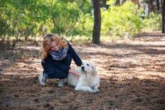 一个女孩使用与她的金毛猎犬 免版税图库摄影