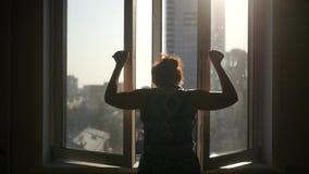 一个女孩关闭窗口的框格,转动笔,以房子和阳光为背景 慢的行动 股票录像