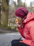 一个女孩吃苹果计算机 免版税库存图片