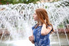 一个女孩听到在您的电话的音乐在喷泉附近 免版税库存图片