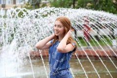 一个女孩听到在您的电话的音乐在喷泉附近 库存照片